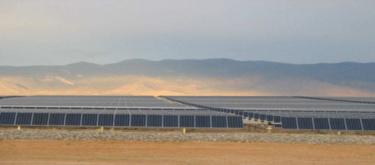 Solar panel farm in front of mountian backdrop